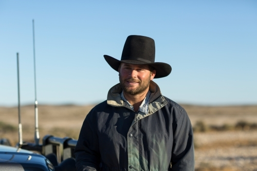 Young man wearing cowboy hat in the outback