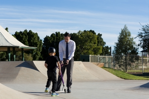 Father and son with scooter at skatepark