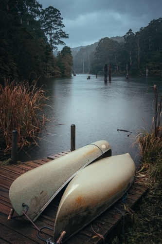 2 Canoes Docked on a Jetty Beside a Remote Lake in the Rain