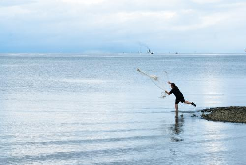 Fisherman throwing bait net on foreshore