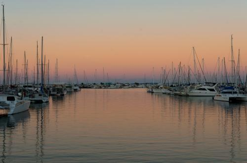 Colourful sunset reflections in a marina with yachts and boats.
