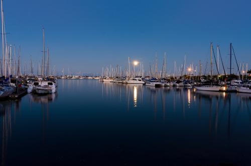 Moon rising over yachts in marina with reflections in water