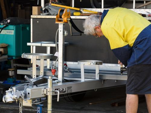 Grey haired man working on drawbar of camper trailer