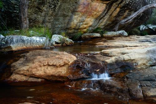 Picturesque creek with water tumbling over coloured sandstone