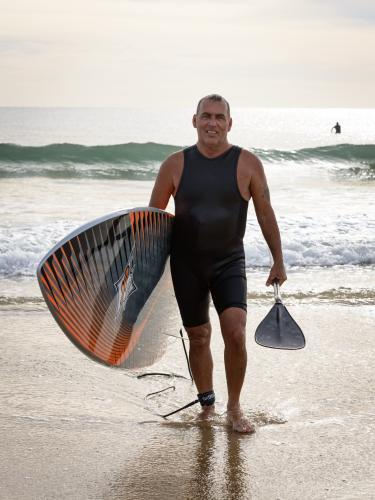 Smiling older man, holding surfboard and paddle