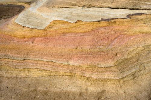 Detail shot of layered pink, yellow and orange sedimentary rock