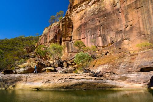Creek in a gorge with orange sandstone rock formation and blue sky