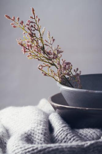 Winter still life of grey bowls, scarf and flowers vertical