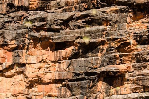 Shot of rocky cliff face with layered orange and dark rock