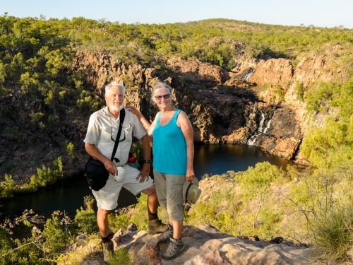 Smiling grey haired man and woman posing on rock with scenic waterfall and plunge pool behind