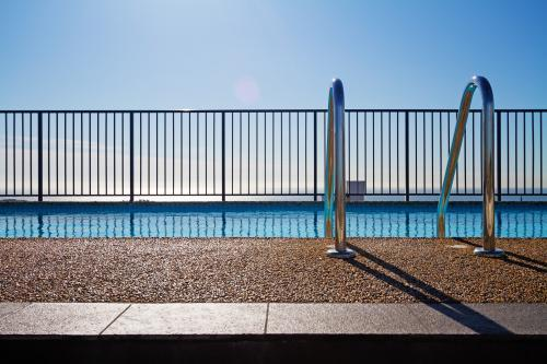 Swimming pool and fence with infinity background and pebble mix edge