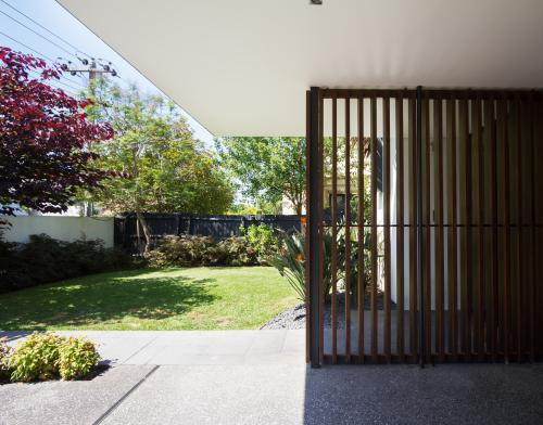Wood screen detail of contemporary home front entrance and garden