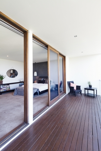 Master bedroom and large glass sliding doors to balcony in luxury Australian home