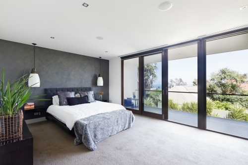 Spacious interior of designer master bedroom in luxury Australian home