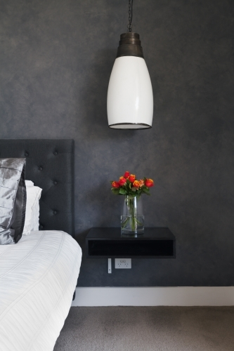 Orange roses on bedside table in contemporary dark bedroom design