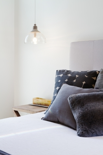 Luxury bedroom details throw pillows and bedside penant light