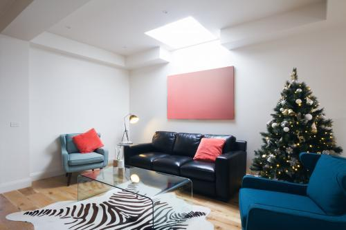 Christmas tree in contemporary living room with coral detail cushions
