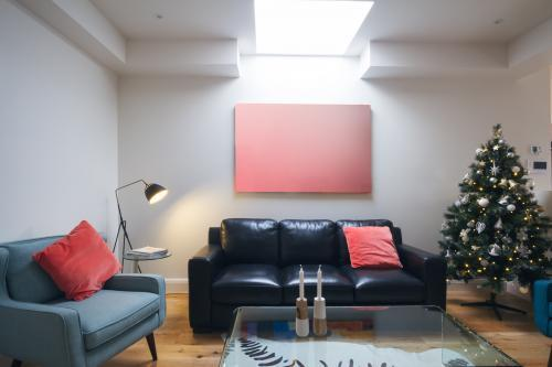 Three seater sofa in living room with christmas tree and blank artwork