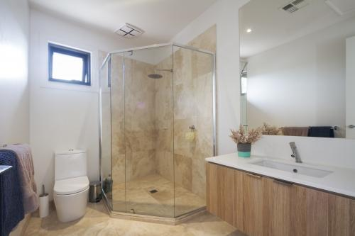 Corner shower marble tiling in contemporary bathroom in luxury house