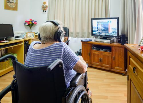 Back view of old grey haired woman in wheelchair watching TV