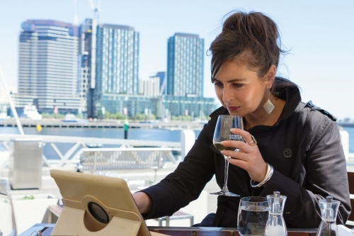 Professional woman working on a tablet over lunch at Docklands in Melbourne
