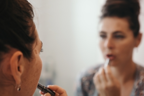 Close up of brunette woman applying makeup with blurred mirror reflection
