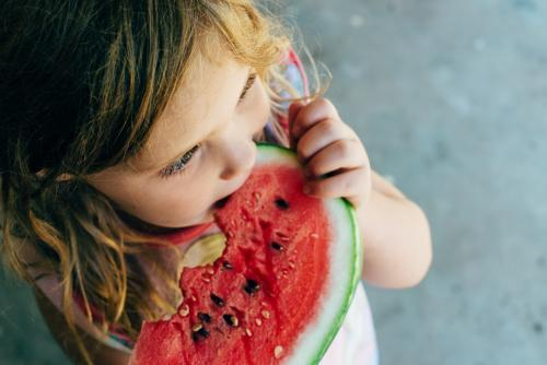 Little girl looking away, eating watermelon