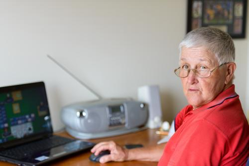 Old person using laptop and looking at camera