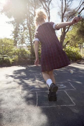 7 year old girl playing hopscotch in school uniform on asphalt