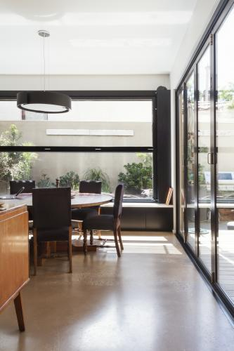 Modern dining room with concrete floor and glass bi fold doors and garden outlook