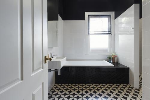 Designer bathroom renovation with monochrome moroccan floor tiles and black bath hob