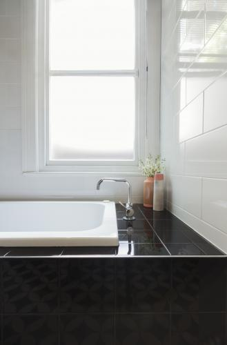 Close up of designer black tiled bath hob with white tiled wall and window behind