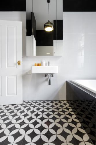 Moroccan styled monochrome bathroom with patterned floor tiles and wall hung vanity