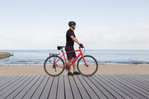 Man standing with bike looking at view of a Melbourne beach