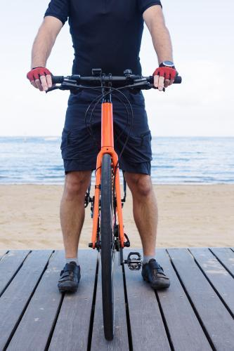 Close up of front on man standing with bicycle at the beach