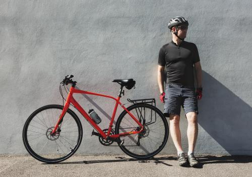 Middle aged cyclist man standing next to his bike with helmet on