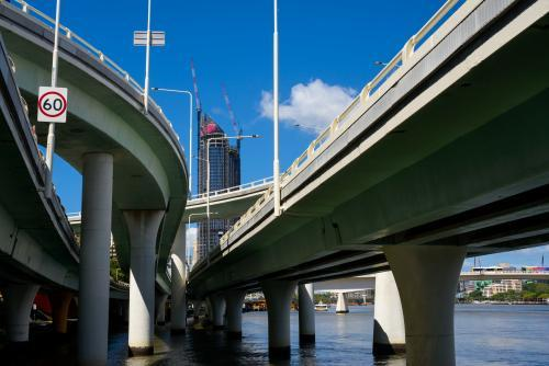 View of a highrise building framed by the Brisbane riverside expressway  bridges and overpasses
