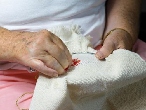 Close up of old woman's hands doing embroidery