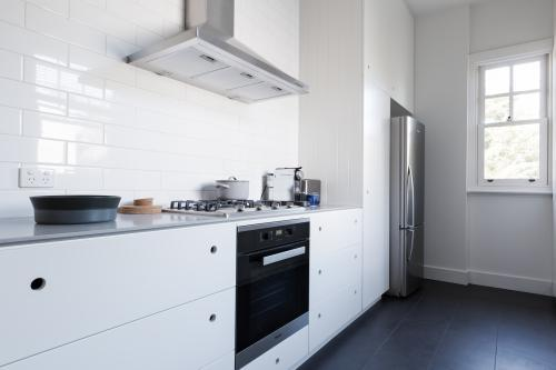 Monochrome clean white kitchen benchtop and cupboards with appliances