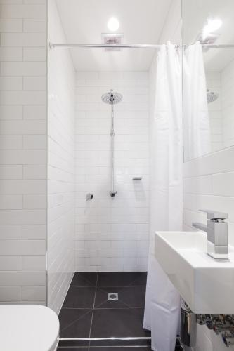 Small renovated white ensuite bathroom with rain shower