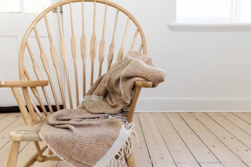 Wooden country style chair with textured throw blanket and negative space for text