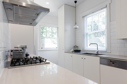 New renovated crisp white galley style kitchen in Australian apartment