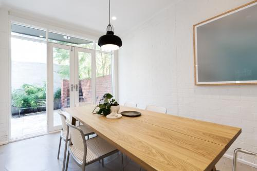 Scandi styled dining room interior with outlook to courtyard through french doors