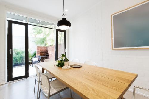 Scandi styled dining room interior with outlook to courtyard through open french doors