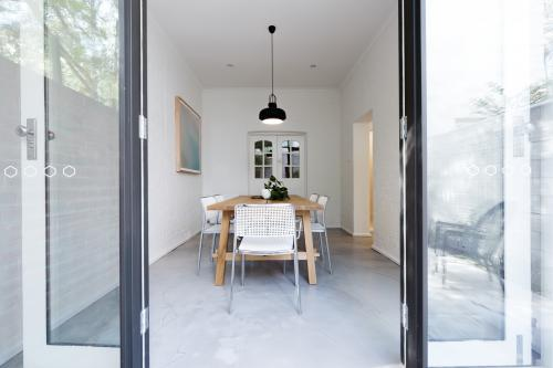 Looking into contemporary scandi styled dining room through french doors from courtyard