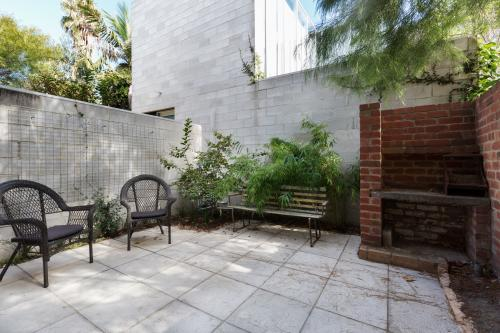 Small apartment courtyard with paving and cane outdoor chairs