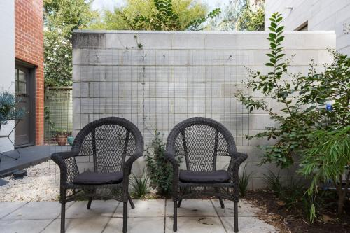 Pair of black cane outdoor chairs in modern paved apartment courtyard