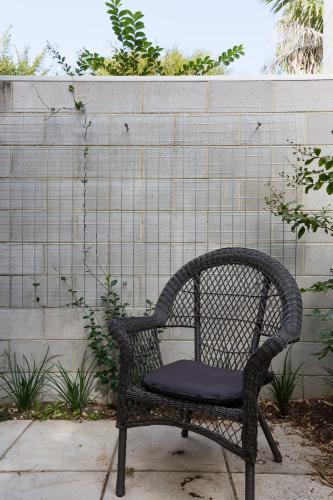 Close up of black cane outdoor chair in courtyard against block brick wall with creeper plant
