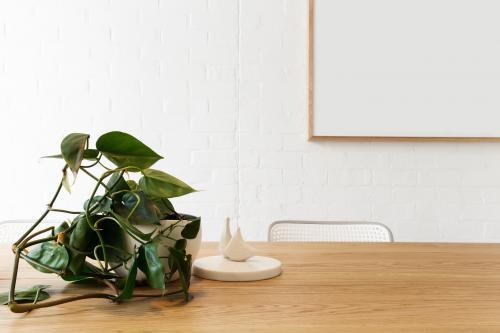 Blank framed artwork on white wall with scandi styled interior objects on wooden table