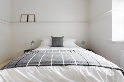 Cloose up of grey woolen throw rug on luxury guest bed in Australian apartment